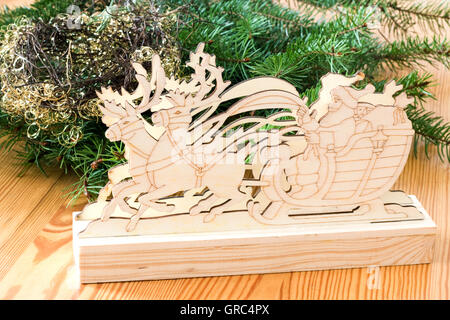 Wooden Santa Claus In A Reindeer Sleigh With Fir Branches - Stock Photo