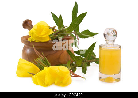 Bottle Of Yellow Bath Liquid Near Evening Primroses With Mortar And Pestle - Stock Photo