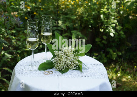 Wedding, Bridal Bouquet With Wedding Rings And Two Glasses Of Sparkling Wine On A White Table - Stock Photo