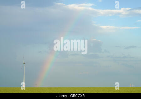 A Rainbog At The Sky And Wind Energy By Wind Turbines - Stock Photo