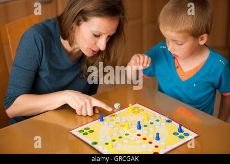Mother and son playing ludo game at home. - Stock Photo