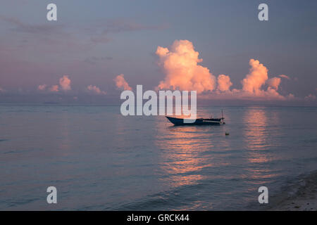 Indonesian Outrigger Canoe On The Sea In Gentle Evening Light, Rosy Cumulus Clouds In The Background - Stock Photo