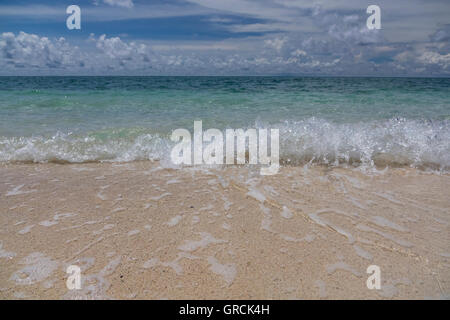 Small Splashing Waves At A White Sandy Beach. Background Blue Sky, White Clouds - Stock Photo