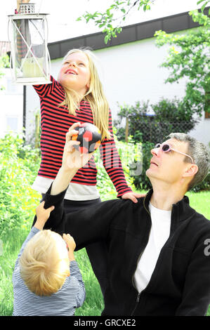 Father With Boy And Girl Playing In The Garden - Stock Photo