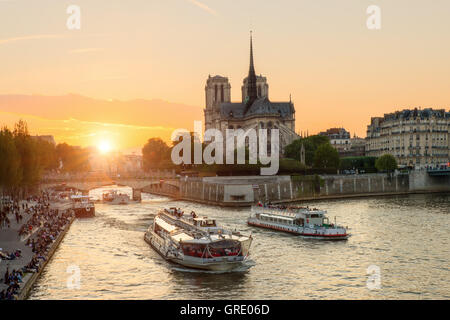 Notre Dame de Paris cathedral with cruise ship in Seine river in Paris, France. Beautiful sunset in Paris, France - Stock Photo