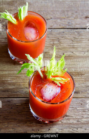 Tomato juice with celery, spices, salt and ice in portion glasses. Bloody Mary cocktail. - Stock Photo