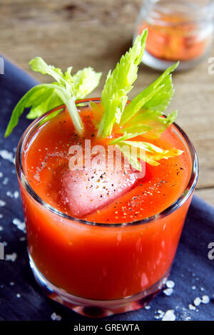 Tomato juice with celery, spices, salt and ice in portion glasses - Stock Photo