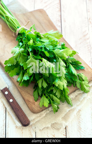 Organic italian parsley closeup on rustic wooden table, healthy vegetarian food - Stock Photo