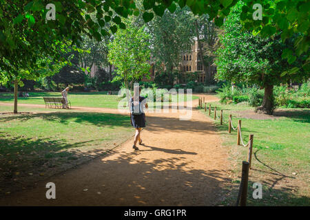 London park, rear view of a young woman wearing a backpack walking through Gordon Square in Bloomsbury on a summer - Stock Photo