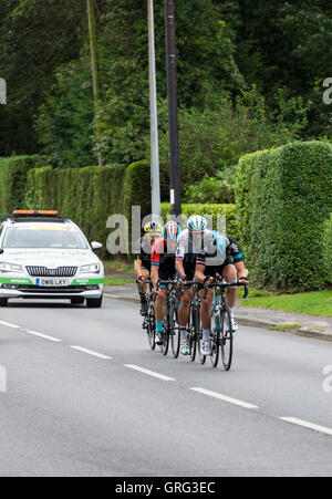 A Small Peloton of Cyclists Followed by a Skoda Support Car in the Tour of Britain Cycle Race in Alsager Cheshire - Stock Photo