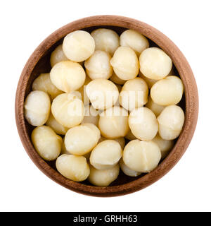 Macadamia nuts in a wooden bowl on white background. Edible seeds without shells. Isolated macro food photo close - Stock Photo