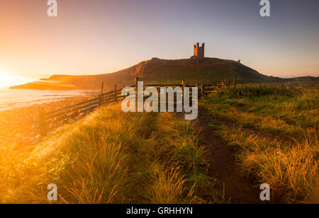 Golden dawn light at the ruins of Dunstanburgh Castle on the coast of Northumberland, England UK - Stock Photo
