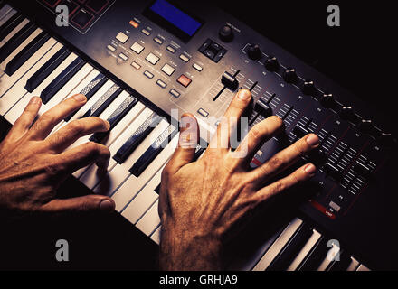 Details of a modern midi keyboard with male hands playing on it. - Stock Photo