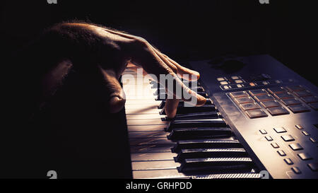 Playing a keyboard, left hand act, accentuated contrasts. - Stock Photo