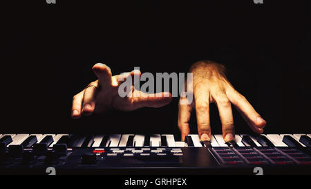 Playing a keyboard, illuminated and accentuated view on hands. - Stock Photo