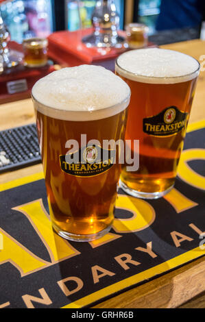 Two pints of real ale in Theakston branded glasses on a Theakston bar towel,  Twice Brewed Inn, Once Brewed, Cumbria, - Stock Photo