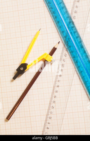 Yellow Drawing compass with black pensil  and rulers on graph paper.Engineering concept. - Stock Photo