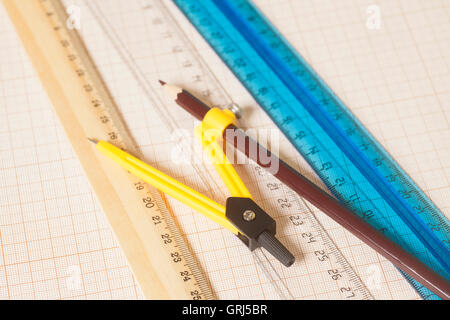 Yellow Drawing compass with black pencil and rulers on graph paper.Engineering concept. - Stock Photo