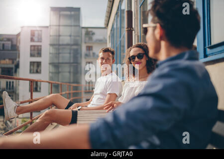 Shot of young woman sitting with her friends at outdoor cafe. Group of young people relaxing in a balcony. - Stock Photo