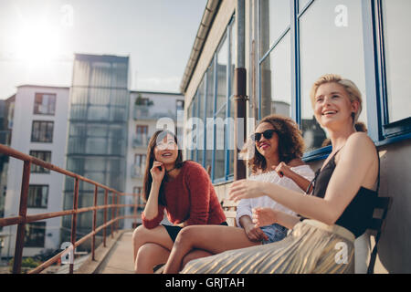 Happy three young female friends sitting in balcony and smiling. Women relaxing outdoors in terrace. - Stock Photo