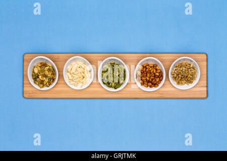 Different types of nuts presented in tater cups on blue background - Stock Photo