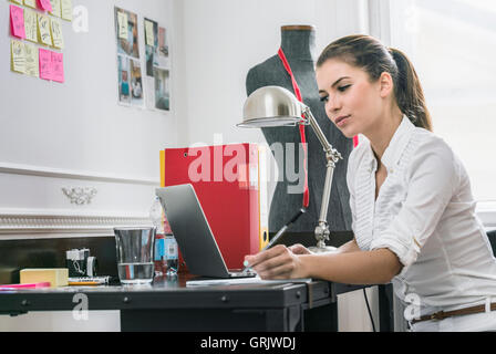 young beautiful woman at a desk working in an office doing admin - Stock Photo