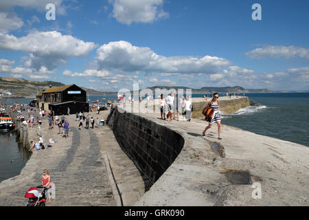 People and woman with striped dress walking on the quay and The Cobb at Lyme Regis on a sunny summer day in Dorset, - Stock Photo