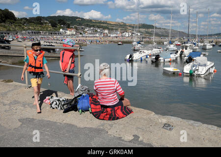 A grandmother and two grandchildren sit on the harbor quay along the Cobb at Lyme Regis Dorset England UK  KATHY DEWITT