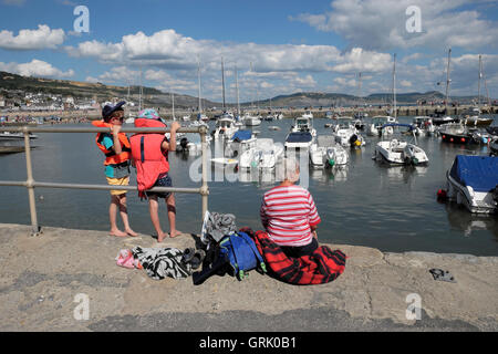 A grandmother and two grandchildren sit on the harbour quay along the Cobb at Lyme Regis Dorset England UK  KATHY DEWITT