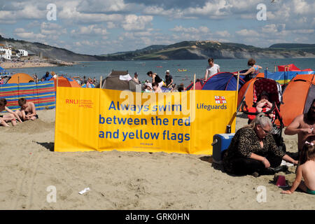 Yellow RNLI Lifeguards safety warning banner to swim between red and yellow flags displayed on the beach at Lyme - Stock Photo