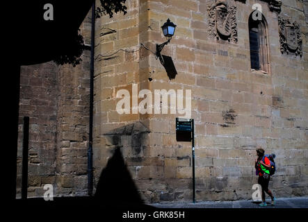 A modern day pilgrim passes the cathedral in Santo Domingo dela Calzada, Spain August 25, 2016. Copyright photograph - Stock Photo