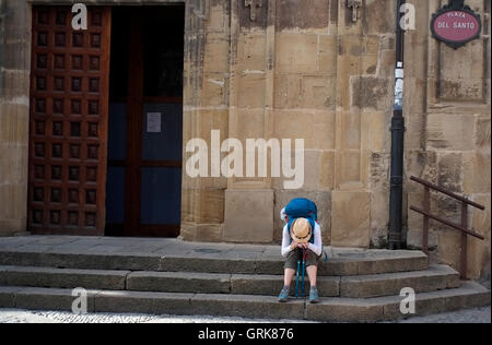 A modern day pilgrim rests in a square in Santo Domingo dela Calzada, Spain August 26, 2016. Copyright photograph - Stock Photo