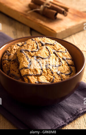 Homemade oatmeal cookies with chocolate in cup over rustic wooden background - Stock Photo