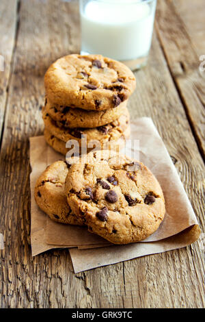 Chocolate chip cookies with milk on paper and rustic wooden table - Stock Photo