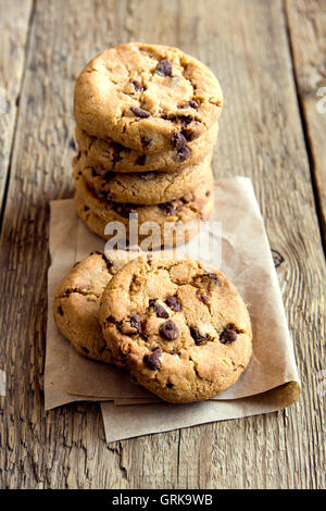 Chocolate chip cookies on paper and rustic wooden table - Stock Photo