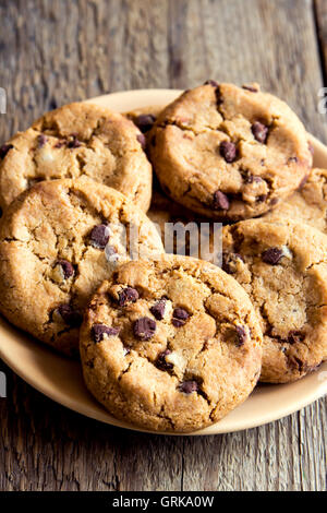 Chocolate chip cookies on plate and rustic wooden table - Stock Photo