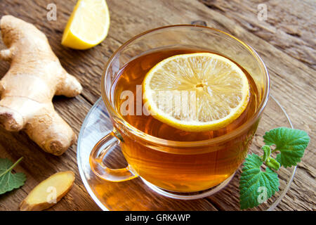 Tea with lemon, ginger, honey and mint leaves in cup over rustic wooden background - Stock Photo