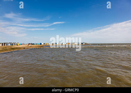Walkers and beach huts on the western beach at Brightlingsea, Essex, UK - Stock Photo
