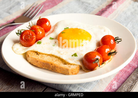 Fried egg on bread and fried tomatoes for breakfast on plate and rustic table - Stock Photo