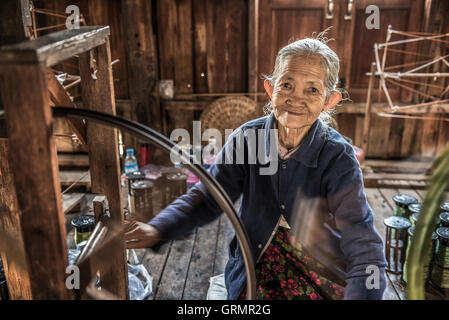 Woman worker weaves fabric in a weaving factory on Inle Lake - Stock Photo