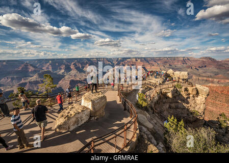 Tourists looking at south rim of Grand Canyon from point of view named 'Mather Point'. - Stock Photo