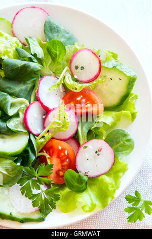 Fresh green spring vegetable salad with cucumber, radish, tomatoes and seeds  over white wooden background close - Stock Photo