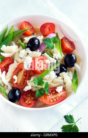 Pasta salad with vegetables, olives and feta over white background - Stock Photo