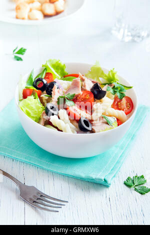 Tuna and pasta salad with fresh tomatoes, olives, herbs in bowl over white wooden background - Stock Photo