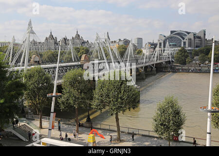 View of Hungerford railway and foot bridges from the south showing River Thames, South Bank and Charing Cross station. - Stock Photo