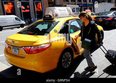 A woman gets into a yellow cab taxi on street of Manhattan.New York City,USA - Stock Photo