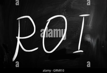 The word 'ROI' handwritten with white chalk on a blackboard - Stock Photo