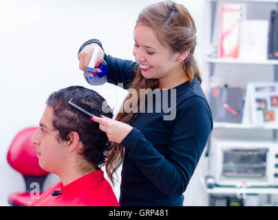Spontaneus and smiling hairstylist is getting wet her next client, comb and spray on her hands - Stock Photo
