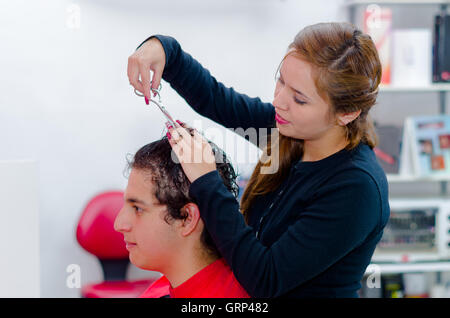 Wet curly hair ready to be cutten, scissors and hands help - Stock Photo