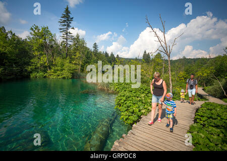 Holidaymakers strolling on a wooden pontoon lined by butterburs along the Korana river (Plitvice Lakes National - Stock Photo